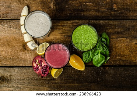 Healthy smoothie - banana-vanilla, pomegranate and orange, spinach and herbs - stock photo