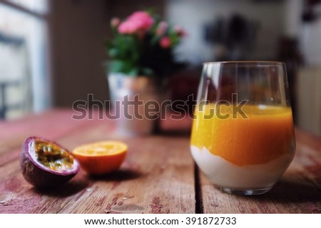 Healthy smoothie; mango orange and passion fruit smoothie with Greek yogurt. Selective focus on smoothie glass. - stock photo