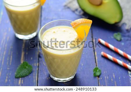Healthy smoothie with orange, banana and avocado, horizontal  - stock photo