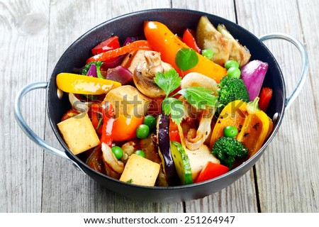 Healthy snack of assorted farm fresh roast vegetables and tofu or soybean curd in a bowl on a rustic grey wooden table - stock photo