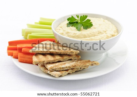 Healthy snack of hummus dip with pita bread slices and vegetables - stock photo