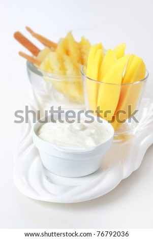 Healthy snack - Pineapple skewer with mango stripes and curd cheese or yogurt - stock photo