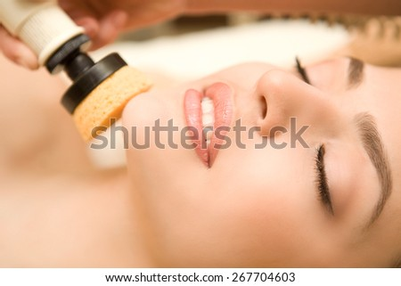 Healthy spa: close-up of a young beautiful relaxing woman having facial treatment ( peeling, cleaning) - stock photo