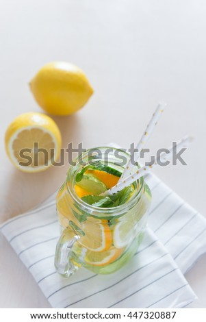 Healthy Spa Water with Fruit. Vitamin water with lemon, mint, celery and cucumber in a jar with straw against a white wood background. - stock photo