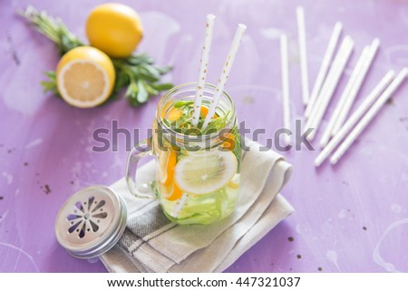 Healthy Spa Water with Fruit. Vitamin water with lemon, mint, celery and cucumber in a jar with straw against a lilac wood background. Available space at right side. - stock photo