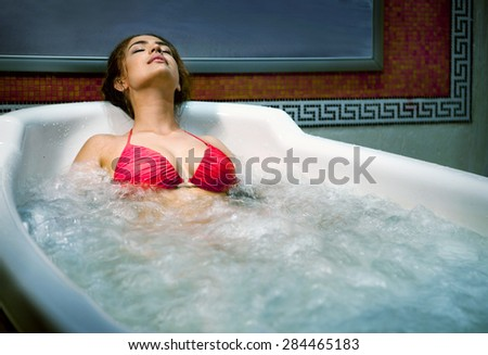 Healthy Spa: Young Beautiful Relaxing Woman Lying in the Bath with Hydro Massage. - stock photo