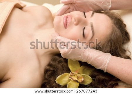 Healthy spa: young relaxing beautiful woman having facial treatment, with orchid in the long brown hair - stock photo