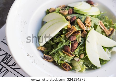 Healthy spinach and arugula salad with cilantro, dried figs, spiced almonds and apple served with a lite vinaigrette. - stock photo