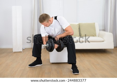 Healthy Sporty Young Man Lifting Weights At Home - stock photo