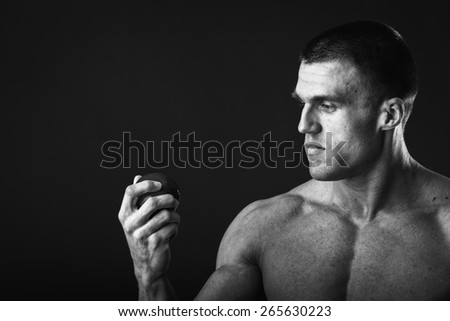 Healthy, strong man bodybuilder on a dark background, holding a fresh juicy fruits. Muscular guy holding apple and pear. Concept of healthy food, fruit, sports nutrition. - stock photo