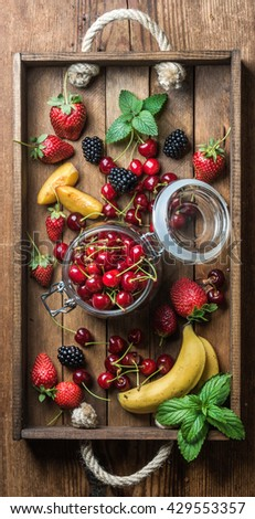 Healthy summer fruit variety. Sweet cherries, strawberries, blackberries, peaches, bananas and mint leaves in rustic wooden tray. Top view - stock photo