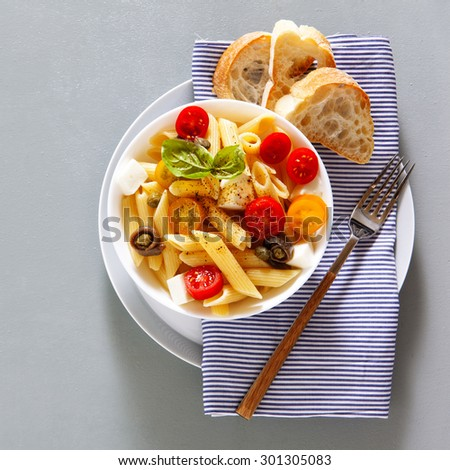 Healthy summer light pasta salad with fresh raw tomatoes, anchovies and capers - stock photo