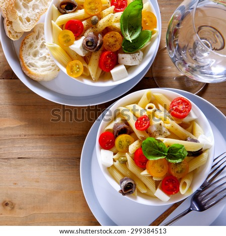 Healthy summer light pasta salad with fresh raw tomatoes, anchovies and capers. glasses with water. on wood - stock photo