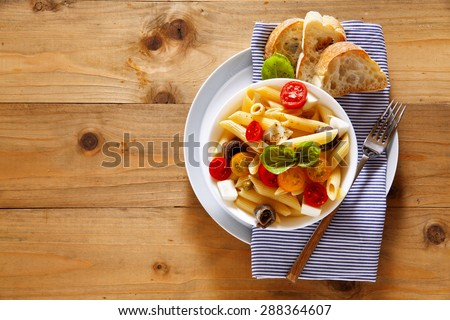 Healthy summer light pasta salad with fresh raw tomatoes, anchovies and capers. on wood. background for restaurants - stock photo