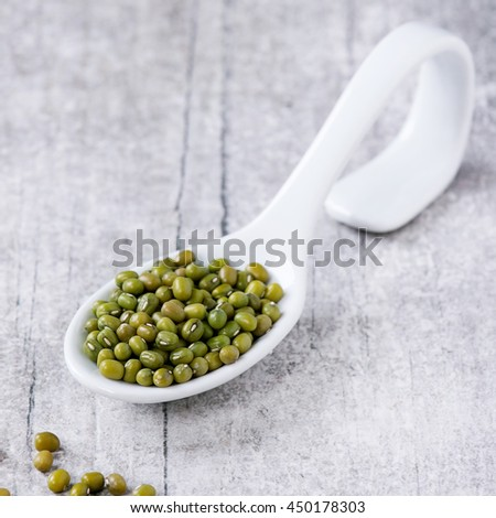 Healthy superfood. Uncooked green mungo beans in white ceramic spoon over white wooden background. Square image - stock photo