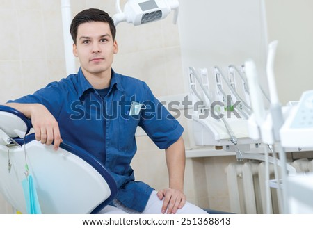 Healthy teeth. Confident professional doctor dentist is sitting and looking into the camera in his medical dental office. Doctor wearing medical clothing. - stock photo
