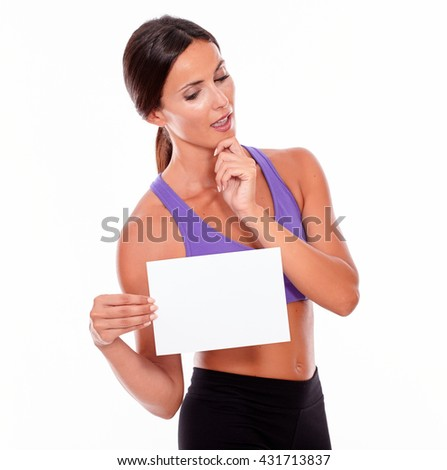 Healthy thoughtful brunette woman gesturing and holding a blank signboard in front of her looking at camera while wearing violet and black gymnastic clothing, isolated - stock photo