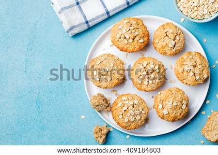 Healthy vegan oat muffins, apple and banana cakes on a white plate Blue stone background Copy space Top view - stock photo