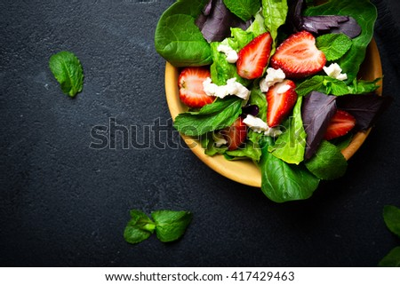 Healthy vegetable salad with strawberry and cheese in wooden bowl on a dark background - stock photo