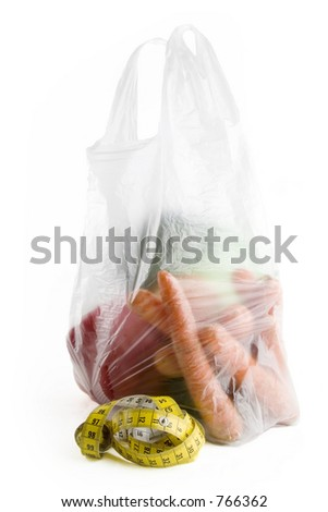 Healthy vegetables in a clear plastic grocery bag on a white background with a tape measure in the foreground - stock photo