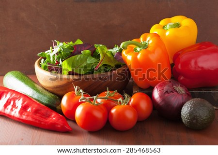 healthy vegetables pepper tomato salad onion avocado on rustic background - stock photo