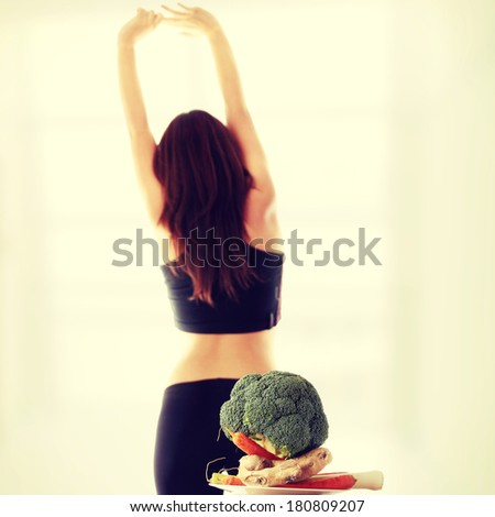 Healthy vegetables with fitness girl in background - stock photo