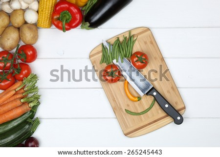 Healthy vegetarian and vegan eating smiling face from vegetables on cutting board with knife - stock photo