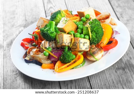Healthy vegetarian cuisine with a tofu salad with colorful roast vegetables including sweet peppers, onion and mushrooms, peas and broccoli - stock photo