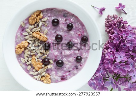 Healthy vegetarian diet meal. Clean eating oatmeal porridge with berries, nuts, and sunflower seeds in white plate. Good food. Served on white kitchen table background with lilac flowers. Rustic style - stock photo