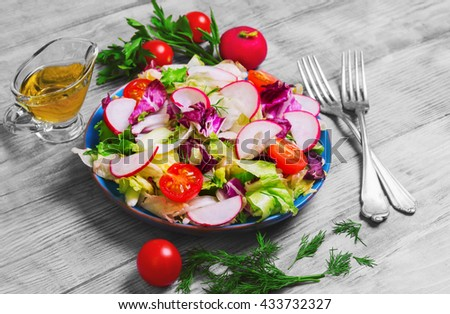 Healthy vegetarian food, fresh vegetables salad with different vegetables radishes, cherry tomatoes, lettuce salad, dill, sauce olive oil, fresh whole radishes,  blue plate, on light wooden background - stock photo