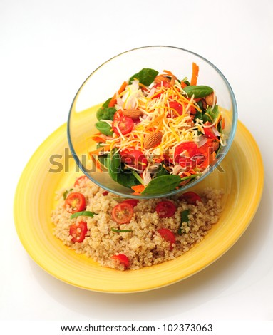 Healthy vegetarian meal that consists of a bowl of salad and a plate of quinoa with tomatoes and basil - stock photo