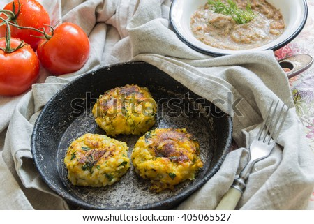 Healthy vegetarian patties made from potatoes, carrots, onions, and green on a background of tomato sauce, selective focus. - stock photo