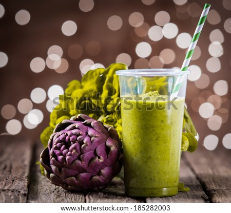 Healthy vegetarian smoothie diet drink with a fresh artichoke and lettuce served on old rustic wooden boards at a perty venue with a bokeh of twinkling lights - stock photo