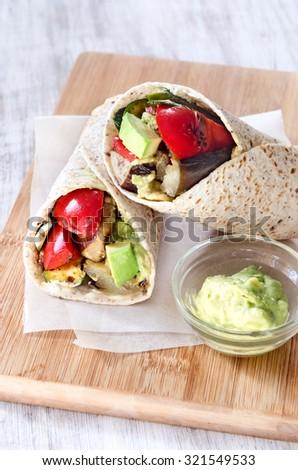 Healthy vegetarian vegan takeaway wraps with roasted vegetables like aubergine eggplant, red bell peppers, avocado  - stock photo