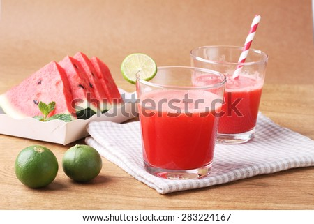 Healthy watermelon lime smoothie and fresh watermelon on a wooden background - stock photo