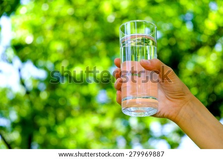 Healthy woman is holding glass of water on natural green background  - stock photo