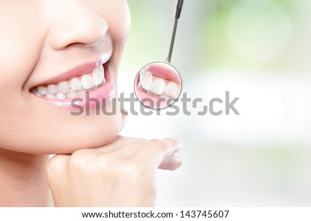 Healthy woman teeth and a dentist mouth mirror with nature green background, asian beauty - stock photo