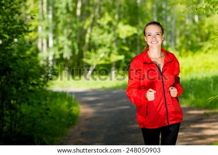 healthy young female athlete running in a summer park smiling and happy while working out - stock photo