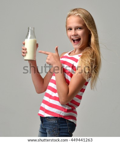 Healthy young girl holding a bottle of milk in her hand and pointing finger on gray background - stock photo