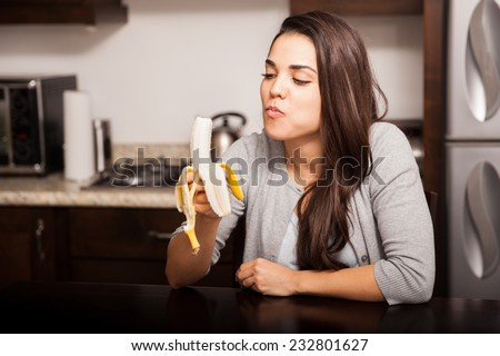Healthy young woman eating a banana while sitting in the kitchen - stock photo