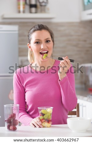 Healthy young woman eating a fruit  on her kitchen counter. - stock photo