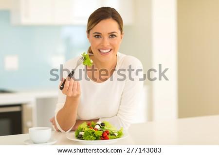 healthy young woman eating green salad at home - stock photo