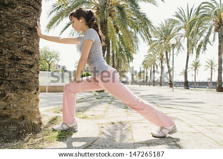 Healthy young woman exercising and stretching leaning on a trunk in a palm tree avenue and listening to music with her head phones during a sunny day. - stock photo