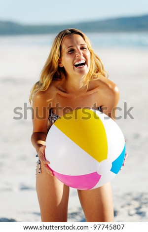 healthy young woman laughing with beachball while on the beach in summer - stock photo