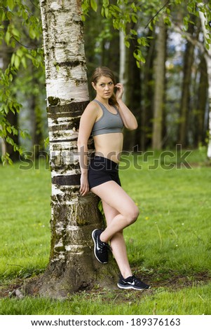 Healthy young woman posing and leaning on a tree outdoors - stock photo