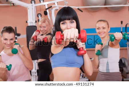 Healthy young women pushing dumbbells forward - stock photo