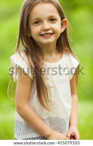 Healthy, yummy childhood concept. Portrait of funny and sweet little girl outdoors with long hair in the wind, milk mustache on face. Close up - stock photo