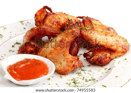 Heap fried on a grill of chicken wings with sauce and spices - stock photo