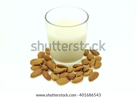 Heap of almonds and a glass of almond milk, on white background. - stock photo