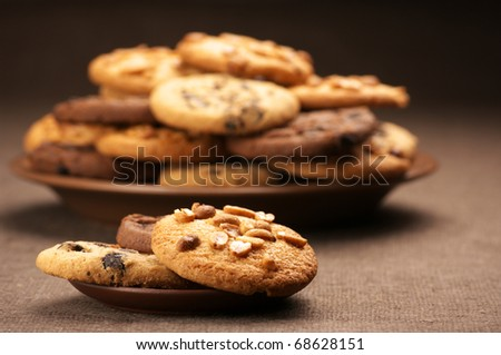 Heap of assorted cookies in brown plate and saucer on brown canvas. - stock photo